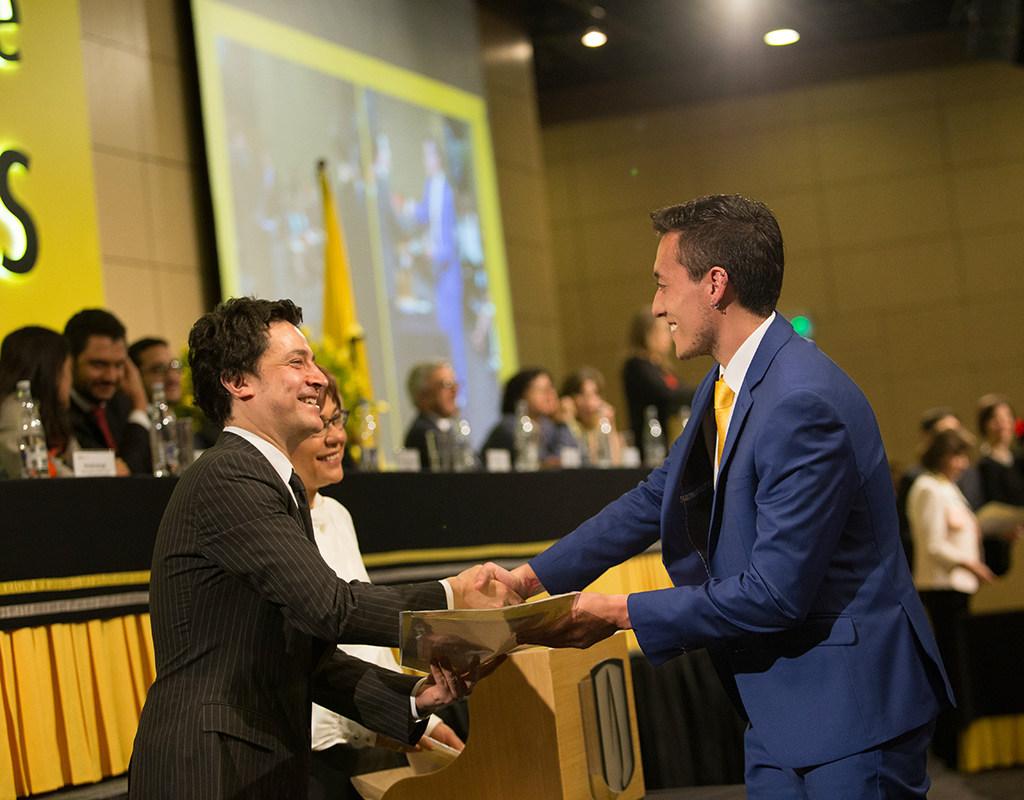 Graduando de la Universidad de los Andes recibiendo diploma de grado
