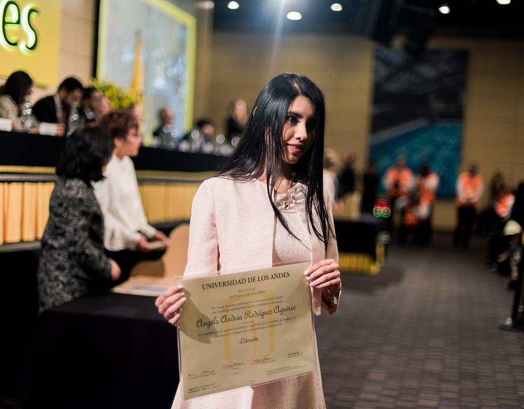 Estudiante de la Universidad de los Andes posando con su diploma de grado