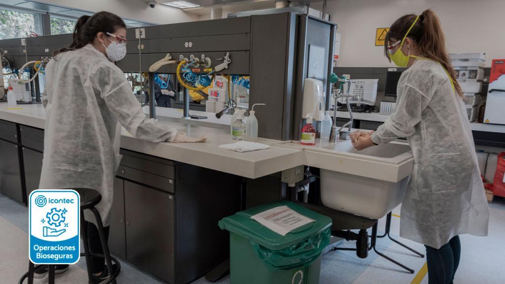 Foto de dos personas cumpliendo con los protocolos en un laboratorio.