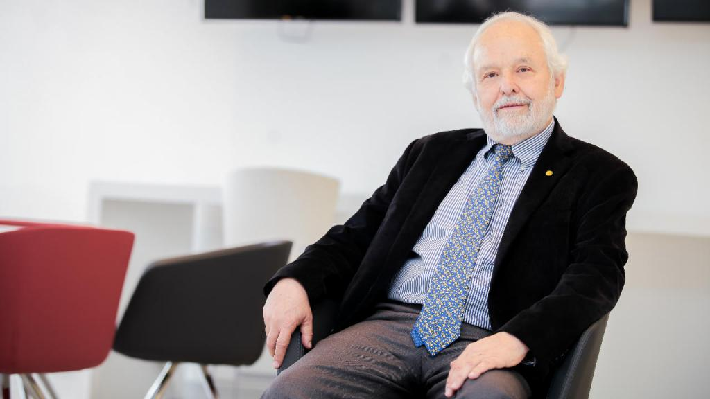 Un señor de 70 años sonrie sentado en una silla