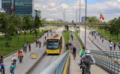 Personas montando bicicleta en una avenida de Bogotá.