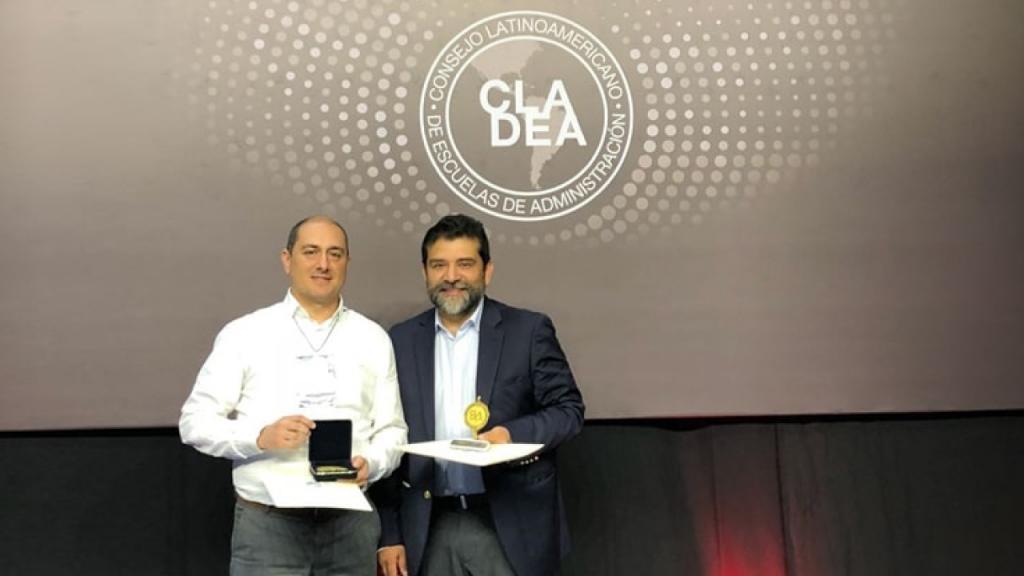 El decano de la Facultad de Administración, Eric Rodríguez, recibe el reconocimiento.