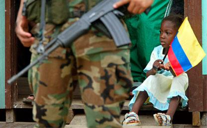 Niña afro sostiene la bandera de Colombia. En primer plano un hombre armado.