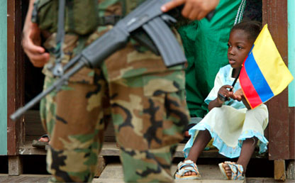 Afrocolombian little girl holding the national flag alongside a soldier