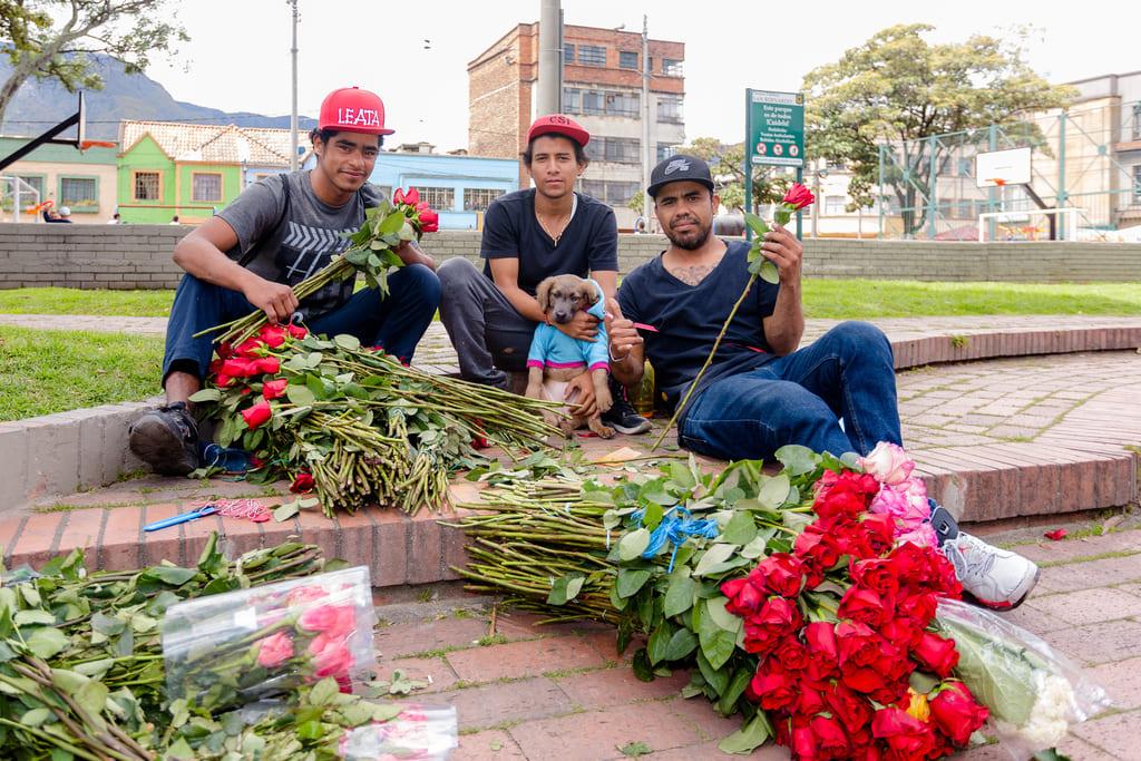Foto de tres venezolanos arreglando unas rosas para vender