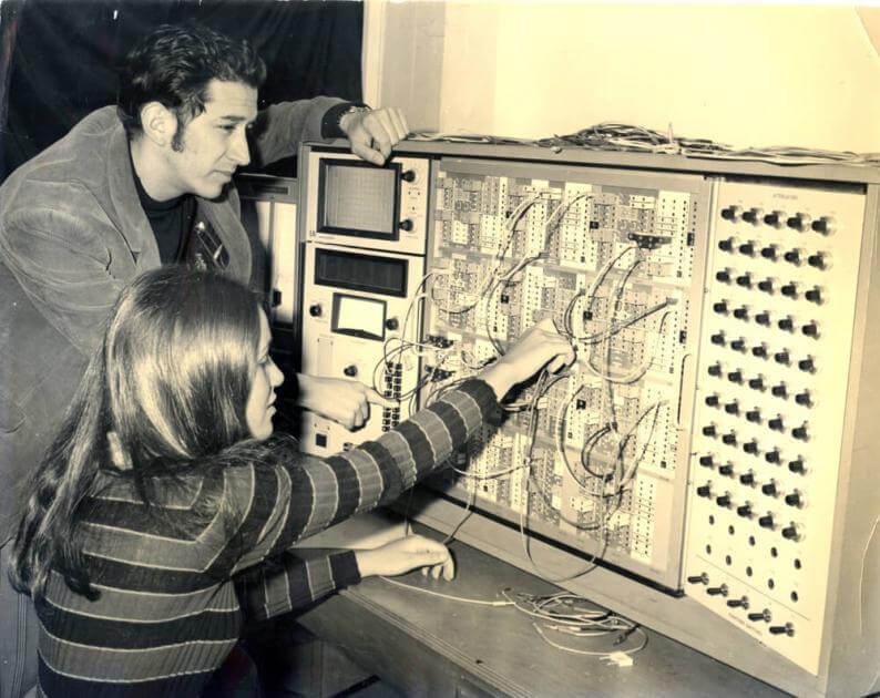 foto antigua en blanco y negro de dos estudiantes trabajando en un computador análogo