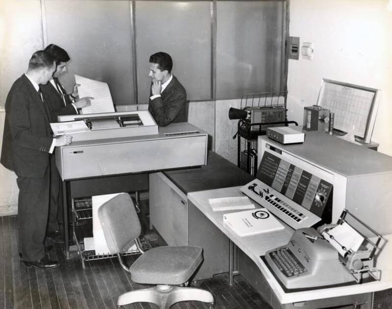 tres hombres en una sala trabajando en un computador IBM-1130 de 1967