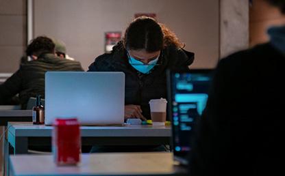 Estudiantes con tapabocas y computadores.