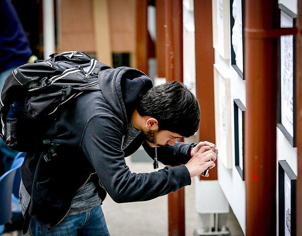 Estudiante toma fotografía a la exposición de dibujos en servilleta.