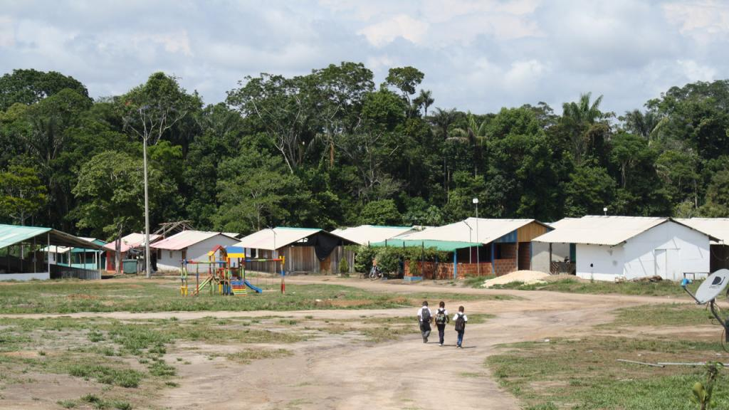 Imagen de caserío con tres niños caminando hacia la escuela.