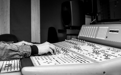 Hands control an audio recording console in the Los Andes studio.