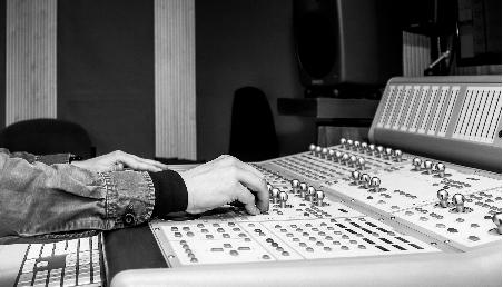 Unas manos manipulan una consola de grabación de audio en el estudio de Los Andes.|