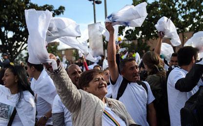 Mujeres y hombres baten pañuelos blancos, pidiendo la paz.