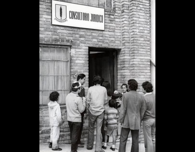 foto antigua en blanco y negro de personas en la entrada al consultorio juridico de uniandes