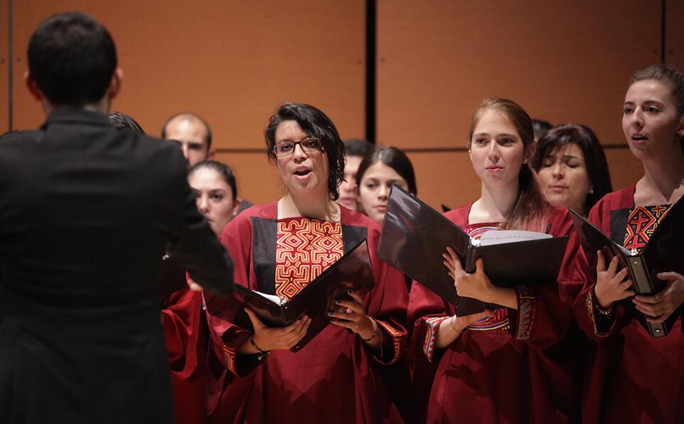 vemos a varias mujeres de un coro interpretando un himno