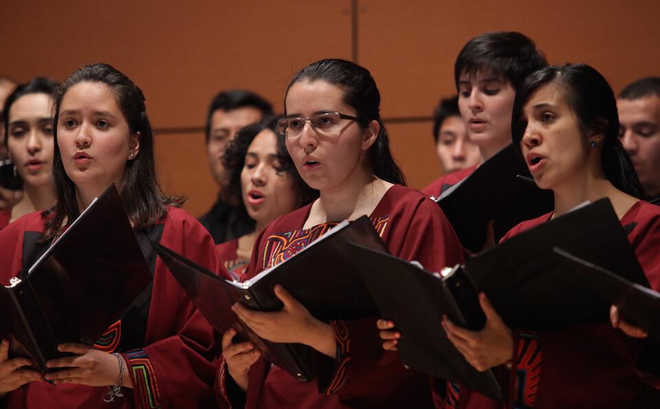 mujeres en un coro cantan un himno