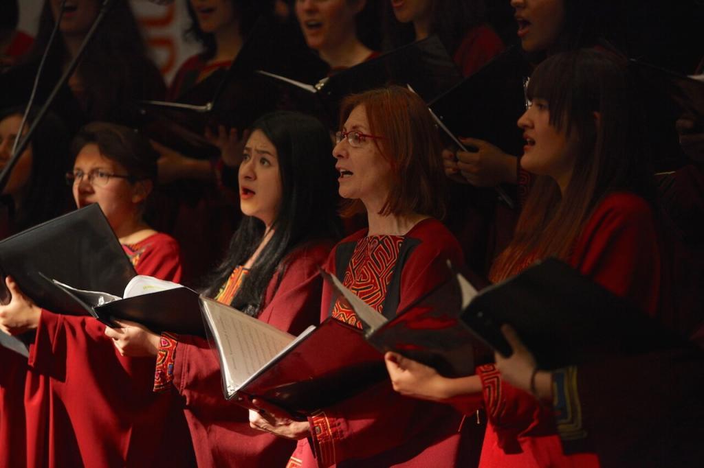 unas mujeres de un coro vestidas con batas vinotinto interpretan un himno