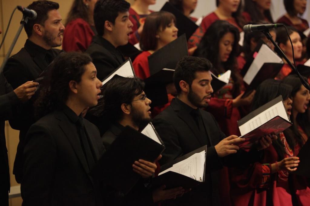 plano medio de un coro interpretando un himno en un auditorio