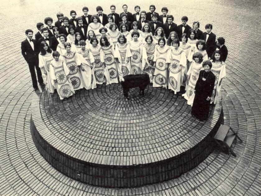foto antigua en blanco y negro de un coro formado en media luna, las muejres con vestido y los hombres con traje y corbatín