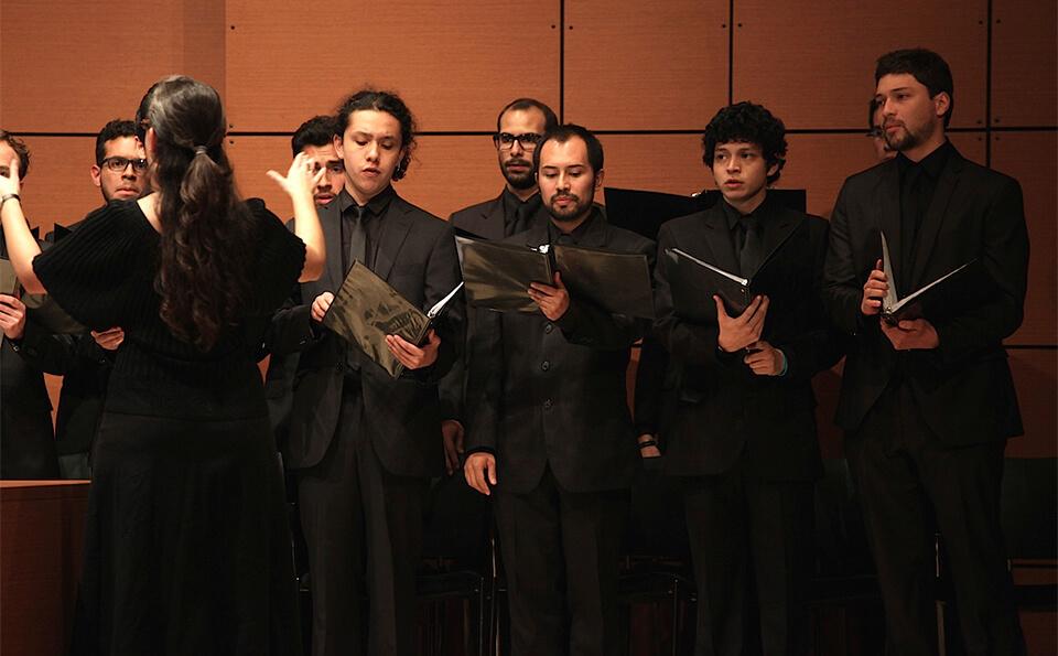 vemos a varios hombres de un coro vestidos de negro cantando un himno en un auditorio