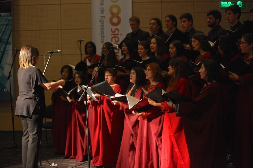 una mujer de negro dirige un coro en un auditorio