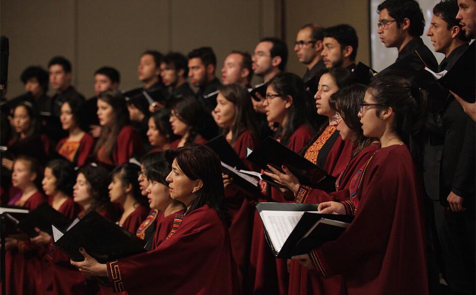 un coro de hombres y mujeres canta un himno en un auditorio