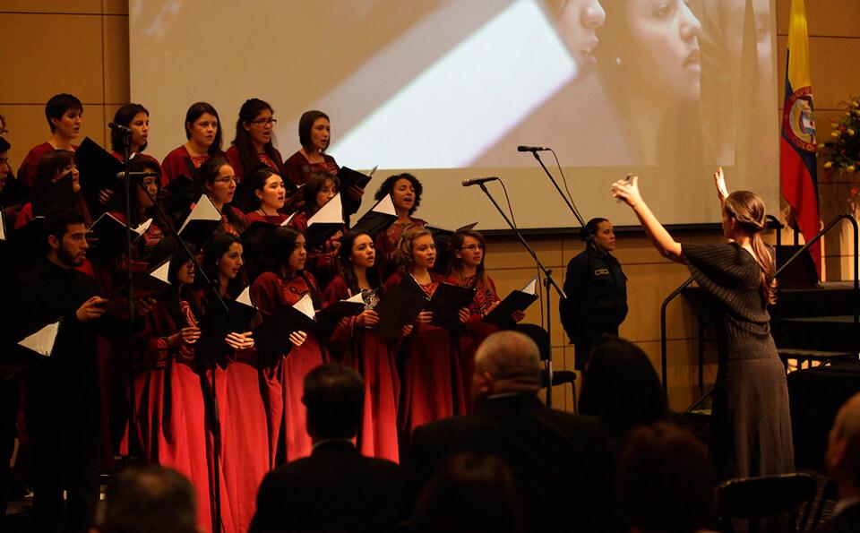 Una mujer de cabello largo vestida de negro dirige  un coro de mujeres con vestido vinotinto