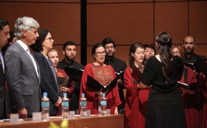 personas con uniforme del coro cantando himno de la universidad de los andes