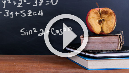 Una manzana podrida sobre dos libros frente a un tablero con signos matemáticos.