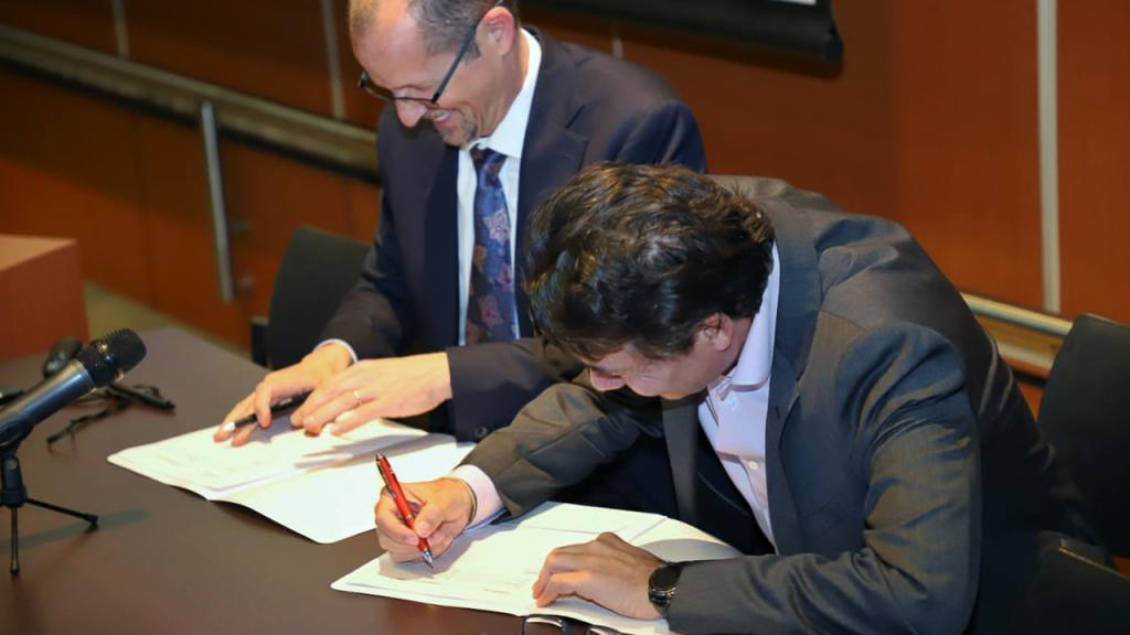 Dos hombres firman acuerdo