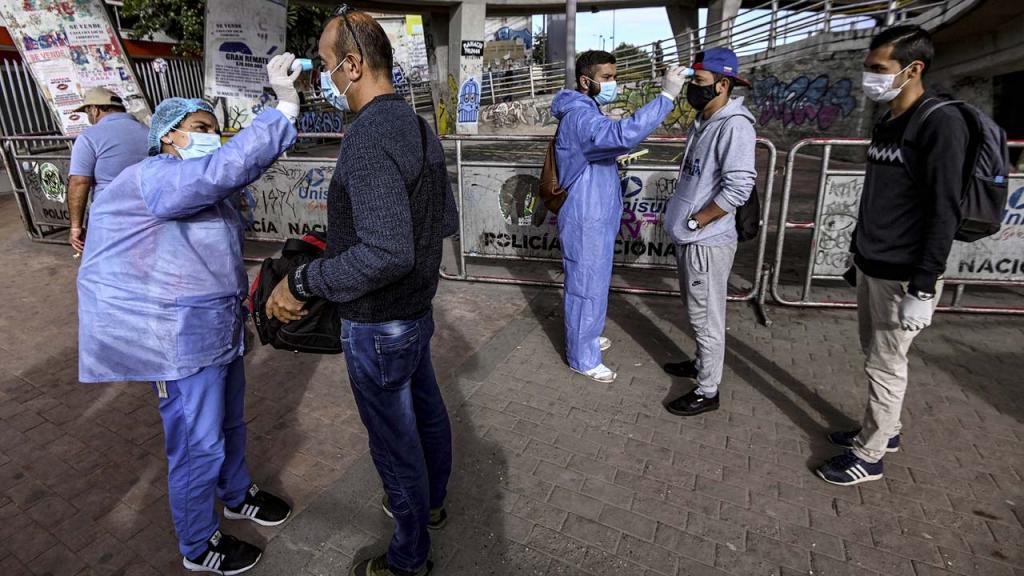 Personal de salud tomando la temperatura a personas en la calle