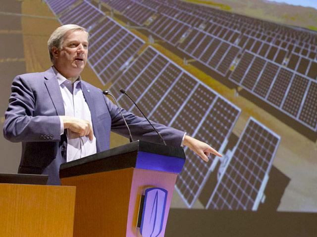 Hombres señalando unos paneles solares.