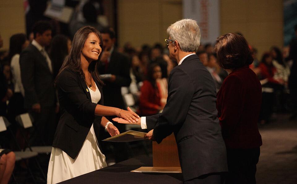 mujer de vestido blanco y saco negro estrecha la mano de un hombre mayor al recibir diploma