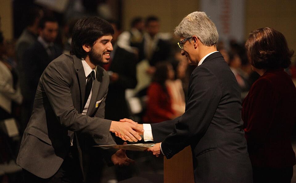 joven de traje gris da la mano a un hombre mayor y le recibe diploma de grado