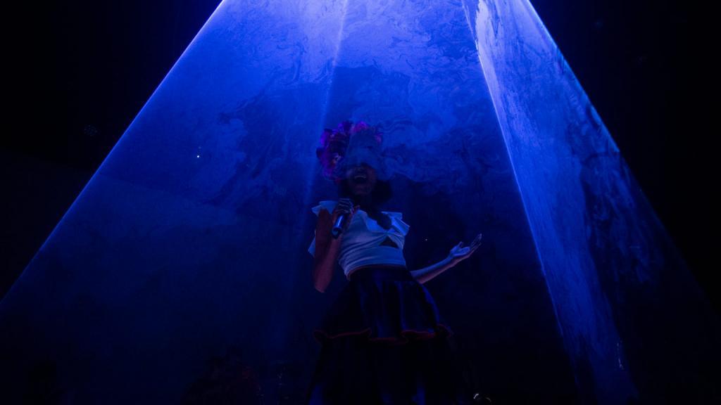 Mujer bajo una luz azul, en un concierto.