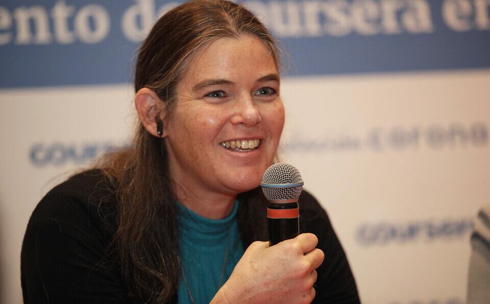 Mujer sonríe con micrófono en mano
