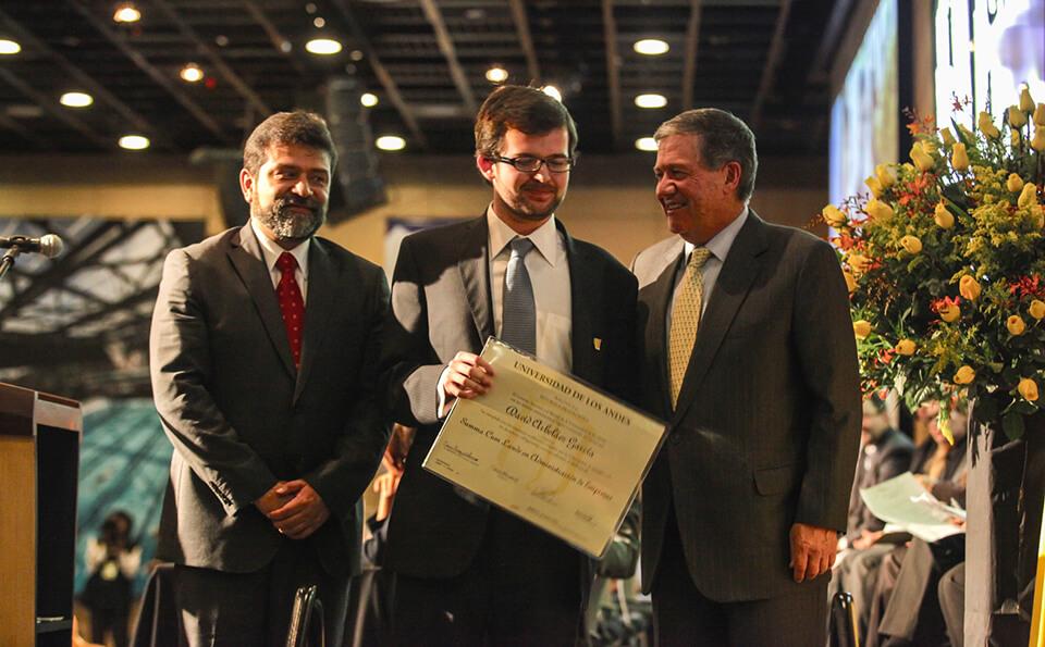 un joven de gafas muestra su diploma junto a dos hombres mayores ellos, rector y decano.