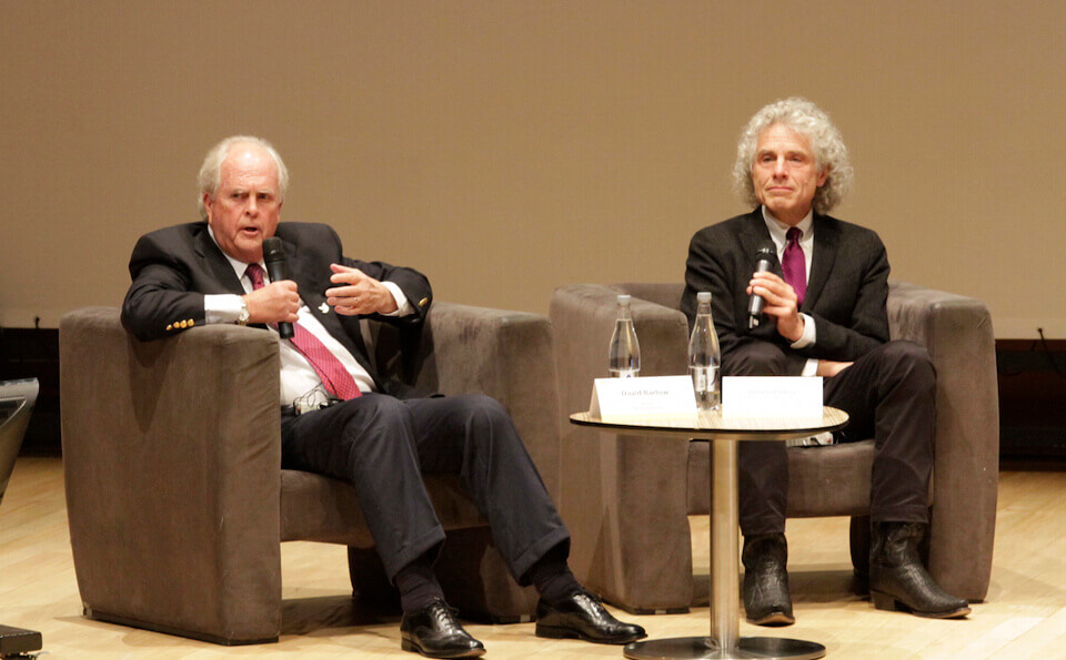 dos hombres mayores sentados en sofá, dando una conferencia en auditorio
