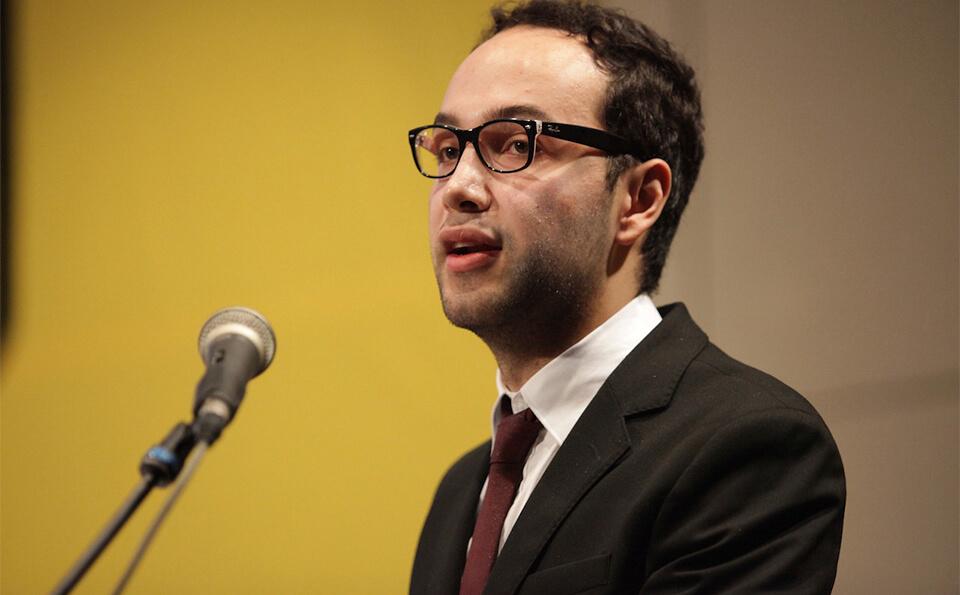 un joven con gafas y traje habla frente a un micrófono