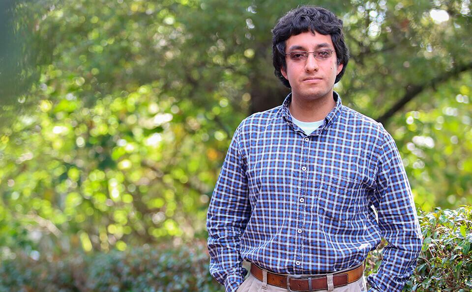 joven estudfiante con camisa de cuadros azul. Usa gafas y tiene sus manos en el bolsillo, en la parte de atrás vemos árboles