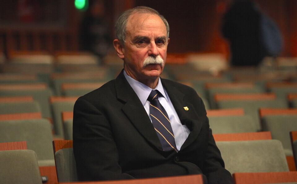 Hombre mayor con traje está sentado en un auditorio vacío