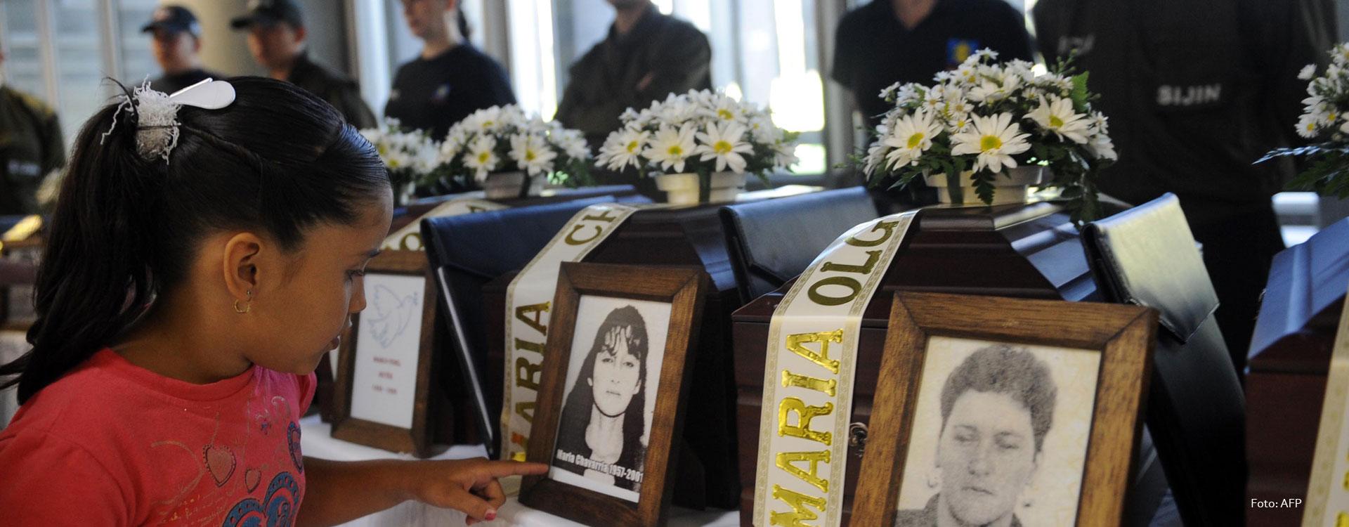 Niña junto a la fotografía de una mujer desaparecida en la ceremonia de entrega de restos.