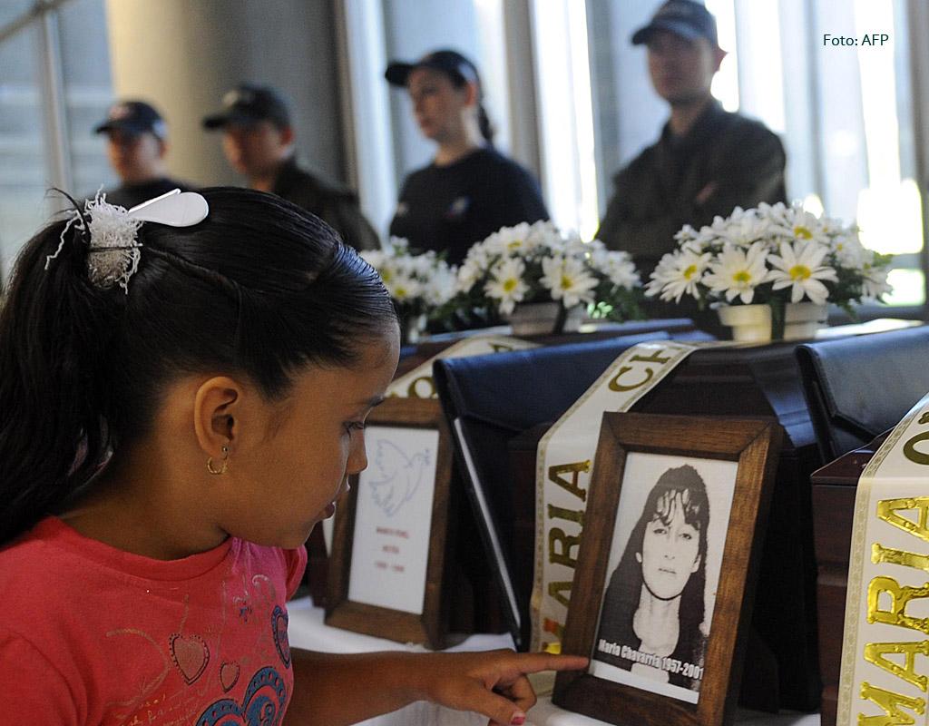 Niña junto a la foto de una mujer desaparecida en la ceremonia de entrega de sus restos.