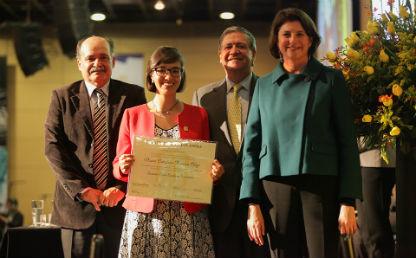 una estudiante sostiene su diploma, la acompañan dos hombres y una mujer en la foto