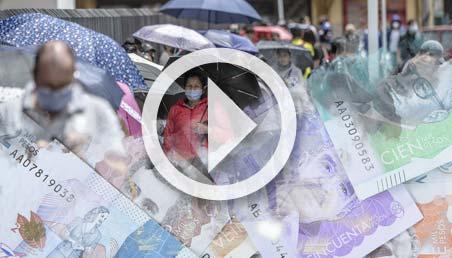 Larga fila de personas usando tapabocas a la entrada de un comercio, con collage de billetes colombianos y símbolo de video