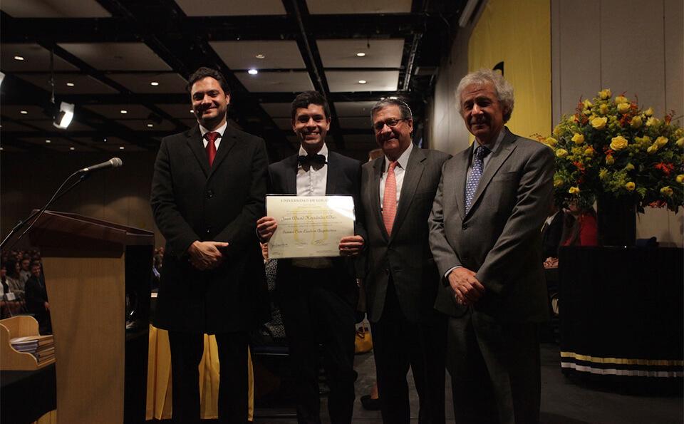 un joven levanta su diploma acompañado de tres hombres directivos de la universidad