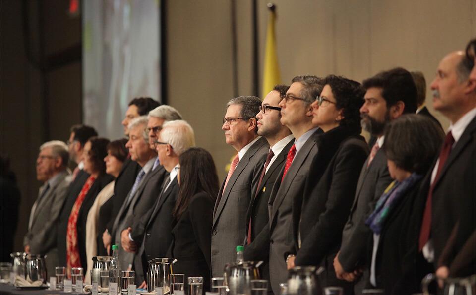vemos a varias personas de pie frente a un auditorio, son directivos en una ceremonia