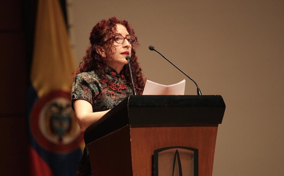 una mujer de pelo crespo y rojo habla frente a un micrófono