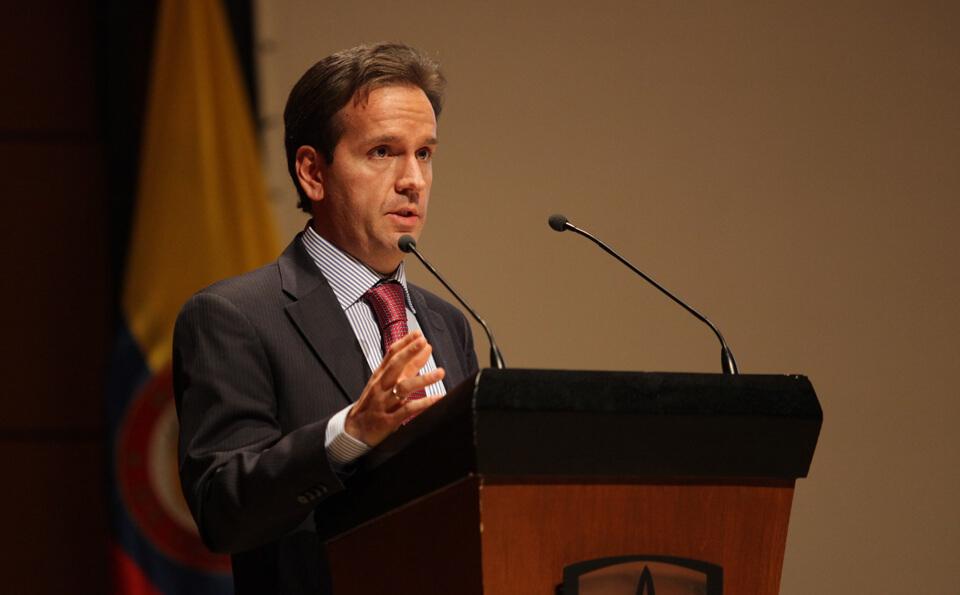 un hombre de traje habla frente a un micrófono