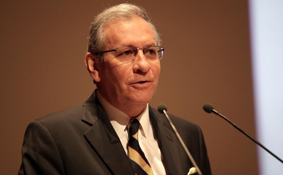 un hombre canoso con gafas habla frente a un micrófono